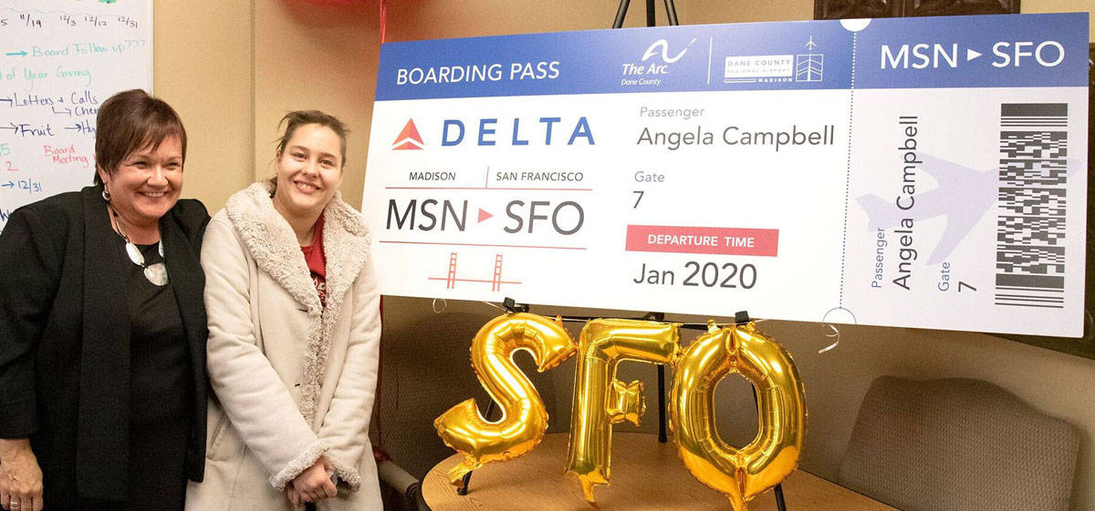 """Job Coach Kathy Walters and self-advocate Angela Campbell pose for a photo with the """"boarding pass"""" for their round-trip flight to San Francisco."""
